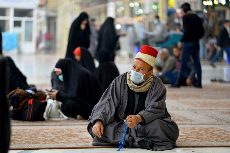 Worshippers wearing masks sit in the courtyard of the shrine of Imam Ali in the central Iraqi holy city of Najaf