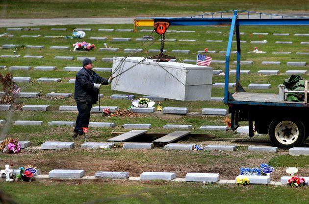 A worker lowers a concrete burial vault into a new grave at Mt. Hope Cemetery in Boston on April 22, 2020. (Photo: Boston Globe via Getty Images)