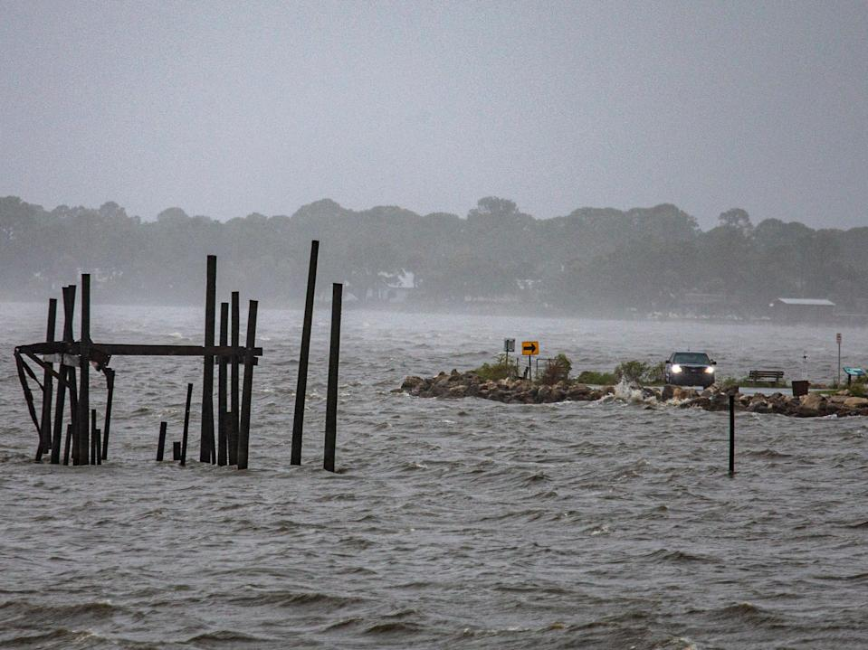 A car drives along the waterfront as Tropical Storm Elsa makes landfall on 7 July 2021 in Cedar Key (Getty Images)