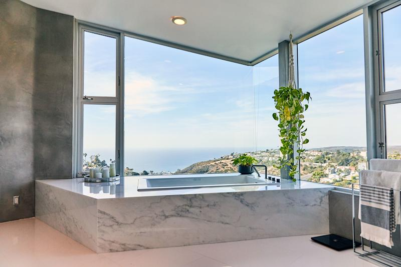 """A friend connected Huston with a marble company in Los Angeles, where he chose the pieces fitted around his massive tub, which he does soak in from time to time. """"I love the way it turned out, the modern look of it,"""" he says. """"And the plants there, too, help out with the good vibe."""""""