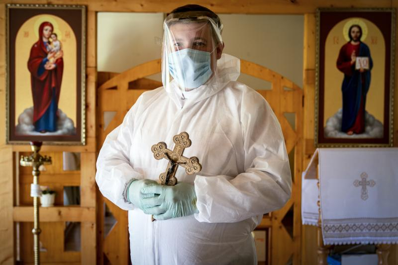In this photo taken on Thursday, May 28, 2020, Ukrainian Greek Catholic Church priest, Father Yaroslav Rokhman wearing protective gear to protect against coronavirus, poses for a photo at a hospice in Ivano-Frankivsk, Ukraine.  Rokhman, a priest in the Ukrainian Greek Catholic Church, is pleased to be able to return to performing one of a cleric's most heartfelt duties. As the coronavirus pandemic's grip on Ukraine slowly recedes, priests received permission on May 22 to again hold services and visit the sick. (AP Photo/Evgeniy Maloletka)