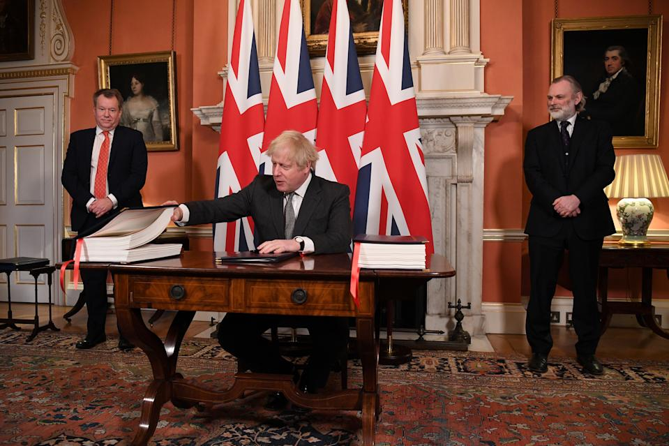 UK chief trade negotiator David Frost and British Ambassador to the EU Tim Barrow look on as Britain's Prime Minister Boris Johnson signs the Brexit trade deal with the EU at number 10 Downing Street in London, Britain December 30, 2020. Leon Neal/Pool via REUTERS