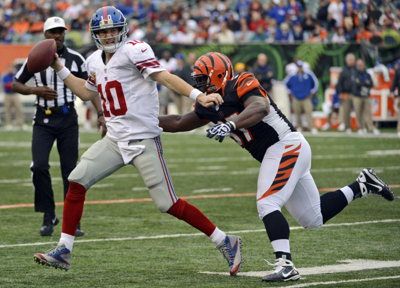 FILE - In this Nov. 11, 2012, file photo, New York Giants quarterback Eli Manning (10) is pursued by Cincinnati Bengals defensive tackle Geno Atkins during the second half of an NFL football game in Cincinnati. Atkins gets a lot of attention every time an opponent watches film trying to figure out how to contain the Bengals defensive tackle. His first selection as a Pro Bowl starter shows what they think of him. (AP Photo/Michael Keating, File)