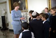 """<p> In 2001, President George W. Bush and First Lady Laura Bush hosted the <a href=""""https://www.insider.com/white-house-hanukkah-party-history-how-it-began#president-george-bush-and-first-lady-barbara-bush-learned-to-play-dreidel-at-the-white-house-in-1990-4"""" rel=""""nofollow noopener"""" target=""""_blank"""" data-ylk=""""slk:first official White House Hanukkah party"""" class=""""link rapid-noclick-resp"""">first official White House Hanukkah party</a>, a tradition that continues today. Previous presidents had paid tribute to the holiday, but the Bushes were the first to make it an official event. </p>"""