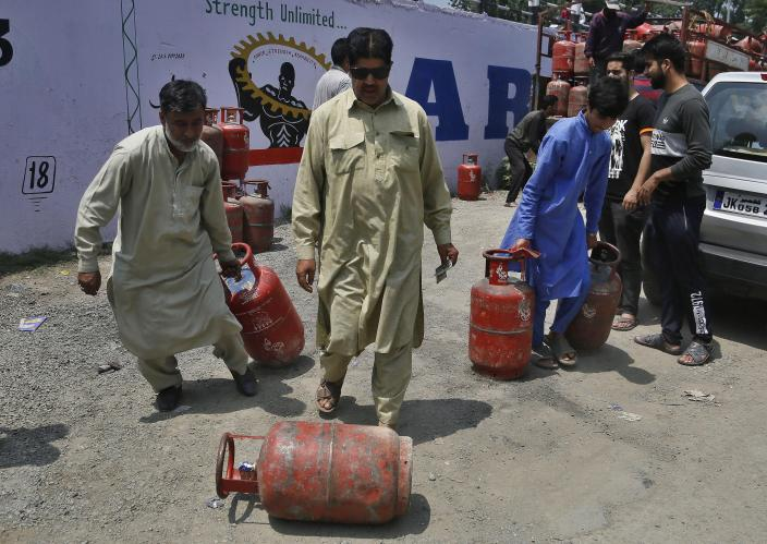 Kashmiri residents take home cooking gas cylinders after buying them in Srinagar, India, Sunday, Aug. 4, 2019. People in Srinagar and other towns in Indian Kashmir thronged grocery stores and medical shops to stock up on essentials. Tensions have soared along the volatile, highly militarized frontier between India and Pakistan in the disputed Himalayan region of Kashmir as India deployed more troops and ordered thousands of visitors out of the region. (AP Photo/Mukhtar Khan)