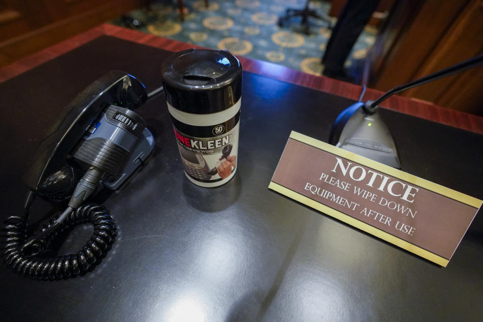 A plaque reminds attorneys to clean equipment on their desks after use in a courtroom at a Manhattan federal courthouse, Friday, March 12, 2021, in New York. (AP Photo/Mary Altaffer)