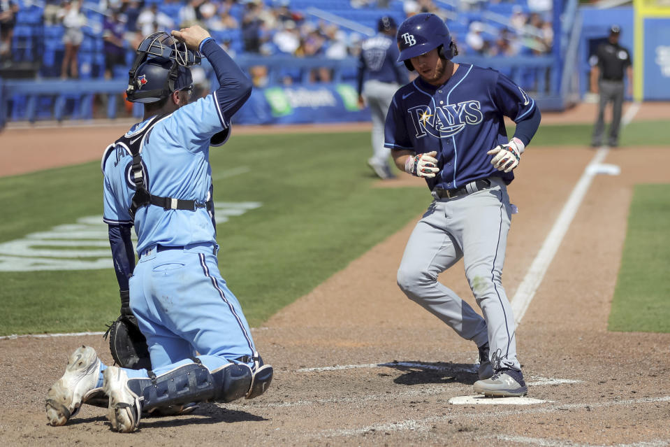 Tampa Bay Rays' Brett Phillips, right, scores on a walk to Manuel Margot in front of Toronto Blue Jays catcher Danny Jansen during the ninth inning of a baseball game Sunday, May 23, 2021, in Dunedin, Fla. (AP Photo/Mike Carlson)