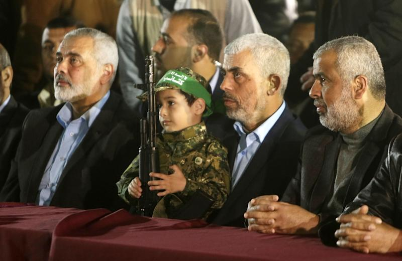Yahya Sinwar (second right), the new leader of Palestinian Islamist movement Hamas in the Gaza Strip and Ismail Haniyeh (left), whom he replaced, sit with the son of slain official Mazen Faqha during a memorial for him on March 27, 2017 in Gaza (AFP Photo/MAHMUD HAMS)
