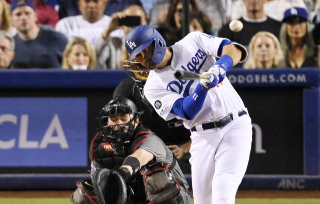 Los Angeles Dodgers' A.J. Pollock, right, hits a sacrifice fly that allowed Corey Seager to score as Arizona Diamondbacks catcher Carson Kelly looks on during the third inning of a baseball game Friday, Aug. 9, 2019, in Los Angeles. (AP Photo/Mark J. Terrill)