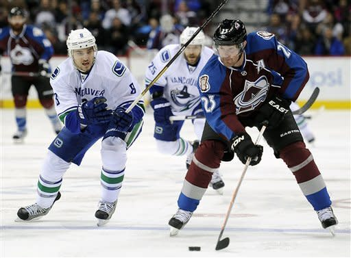 Vancouver Canucks defenseman Chris Tanev, left, tries to defend against Colorado Avalanche right wing Milan Hejduk, right, of the Czech Republic, in the first period of an NHL hockey game on Sunday, March 24, 2013, in Denver. (AP Photo/Chris Schneider)