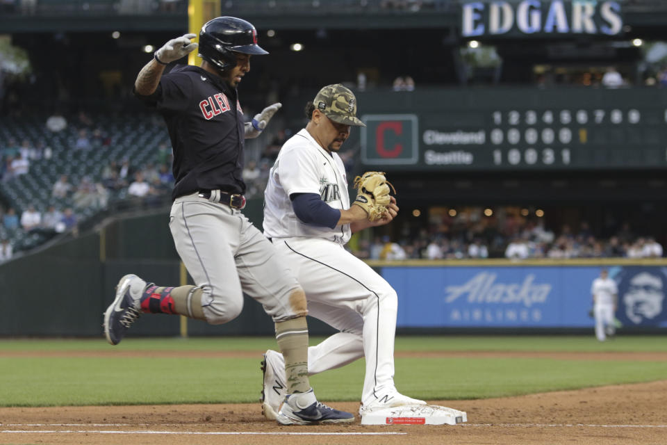 Seattle Mariners starting pitcher Justus Sheffield beats Cleveland Indians' Eddie Rosario to first base for an out during the sixth inning of a baseball game Saturday, May 15, 2021, in Seattle. (AP Photo/Jason Redmond)