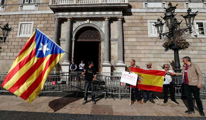 A man holding a Catalan separatist flag looks at men holding a Spanish flag outside the Catalan regional government headquarters in Barcelona (Reuters)