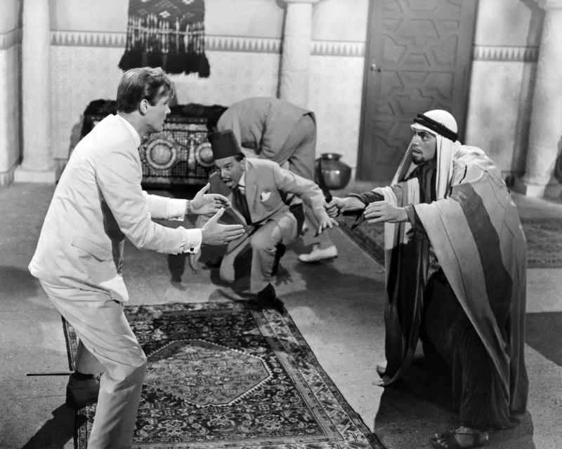 English actor Roger Moore (left) as Simon Templar in a fight scene from 'The Wonderful War', an episode in the British spy thriller TV series 'The Saint', directed by Robert S Baker, 1964. Templar's assailants include Alec Mango (1911 - 1989, centre) as Abdul Aziz, and John Bennett (1928 - 2005, right) as Rashid. (Photo by Silver Screen Collection/Getty Images)