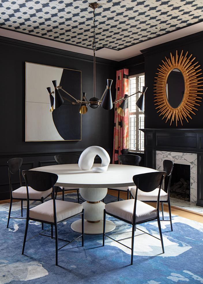 The starting point for the dining room was Benjamin Moore Black Berry walls. The deep blue-black provided a dramatic backdrop that allowed patterns to leap off the walls, ceiling, and floor. Lindsay's Navy White Grasscloth was used to create a faux tray ceiling accented with Farrow & Ball Calamine paint. Jill pumped up the volume in the dining room with the artist's Blue Wool Silk Rug and Porter Teleo draperies, Oly Studio dining chairs, a Mr. Brown London honed Carrara marble table, a Julian Chichester light fixture, and a mirror by Made Goods.