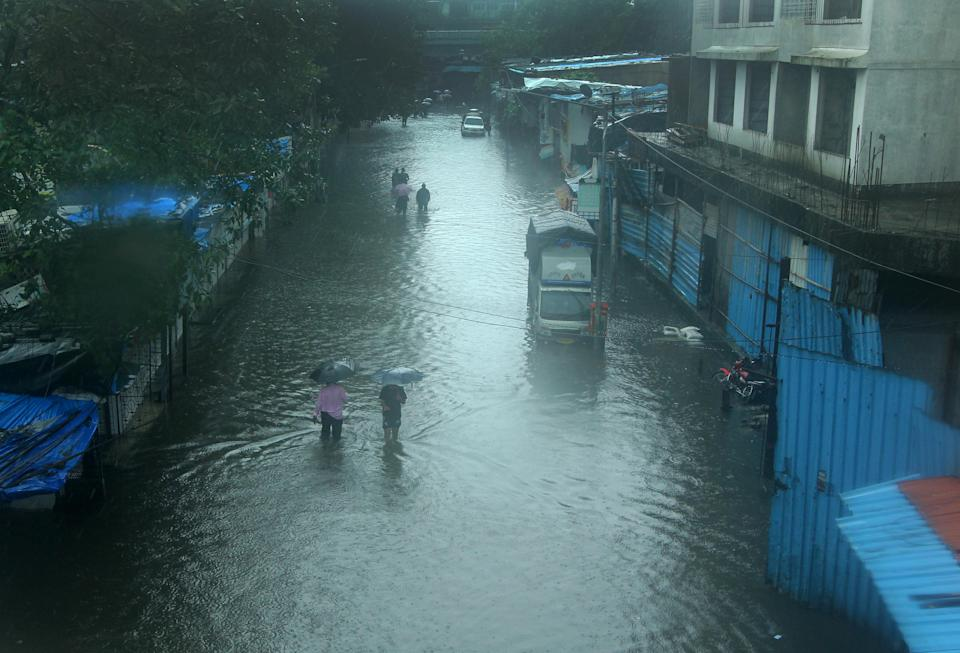 People brave knee deep water along a flooded road in Mumbai. (Photo by Arun Patil)