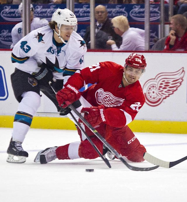 San Jose Sharks forward John McCarthy (43) forces Detroit Red Wings forward Tomas Tatar (21) to the ice, as they fight for the puck during the first period of an NHL hockey game in Detroit, Mich., Monday, Oct. 21, 2013. (AP Photo/Tony Ding)