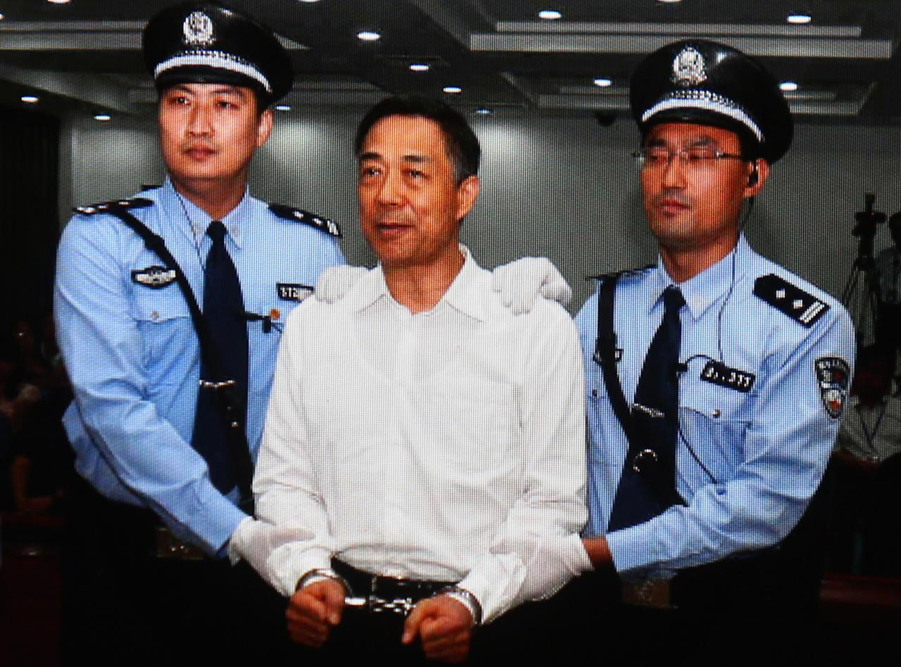 BEIJING, CHINA - SEPTEMBER 22: A screen shows the picture of the sentence of Chinese politician Bo Xilai (Center) on September 22, 2013 in Beijing, China. The Jinan Intermediate People's Court announced Bo Xilai, former member of the CPC Central Committee Political Bureau, was sentenced to life imprisonment on Sunday for bribery, embezzlement and abuse of power. (Photo by Feng Li/Getty Images)