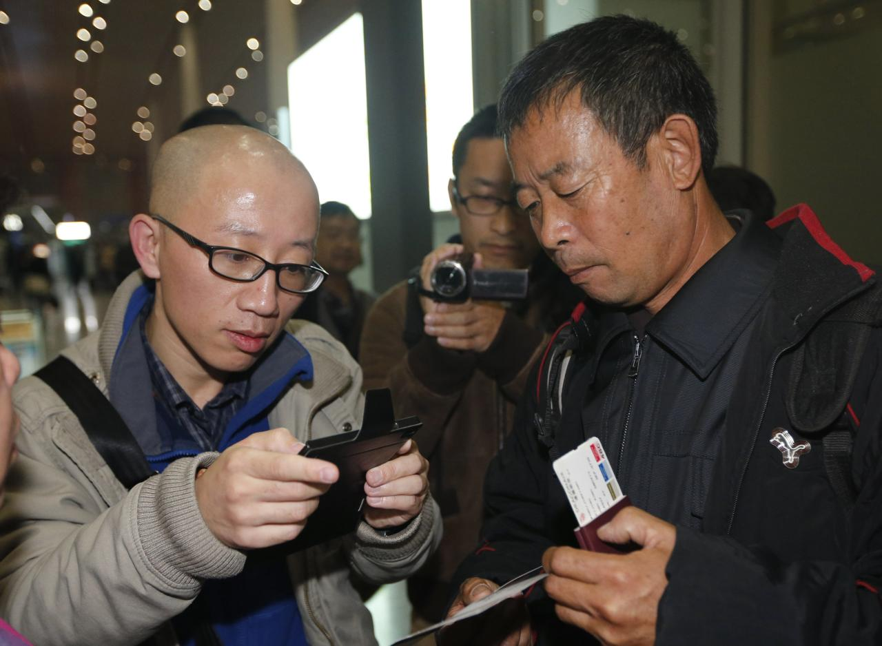 Chinese dissident Hu Jia (L) uses his mobile phone as he talks with Chen Guangfu, brother of Chinese political dissident Chen Guangcheng, who is leaving for the U.S. to meet Chen, at Beijing airport November 6, 2013. Chen, a legal advocate who campaigned against forced abortions, made international headlines last year when he escaped house arrest and found refuge at the U.S. embassy in Beijing. REUTERS/Kim Kyung-Hoon (CHINA - Tags: POLITICS)