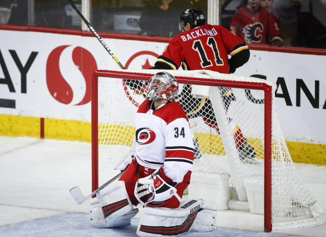 Carolina Hurricanes goalie Petr Mrazek, left, of the Czech Republic, reacts as Calgary Flames' Mikael Backlund, of Sweden, celebrates his game-winning goal in overtime NHL hockey action in Calgary, Tuesday, Jan. 22, 2019. (Jeff McIntosh/The Canadian Press via AP)