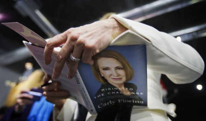 <p>Republican presidential candidate Carly Fiorina autographs a copy of her book for Mike Anderson, of Nashua, N.H., not pictured, during a campaign event at the Aviation Museum of New Hampshire, Feb. 3, 2016, in Londonderry, N.H. <i>(Photo: /David Goldman/AP)</i></p>