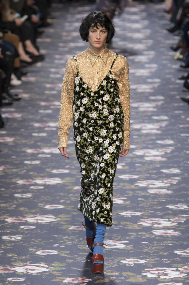 <p>A model at Rochas paired a summery floral dress with a shimmering gold button-up blouse. </p><p><i>(Photo: ImaxTree)</i></p>