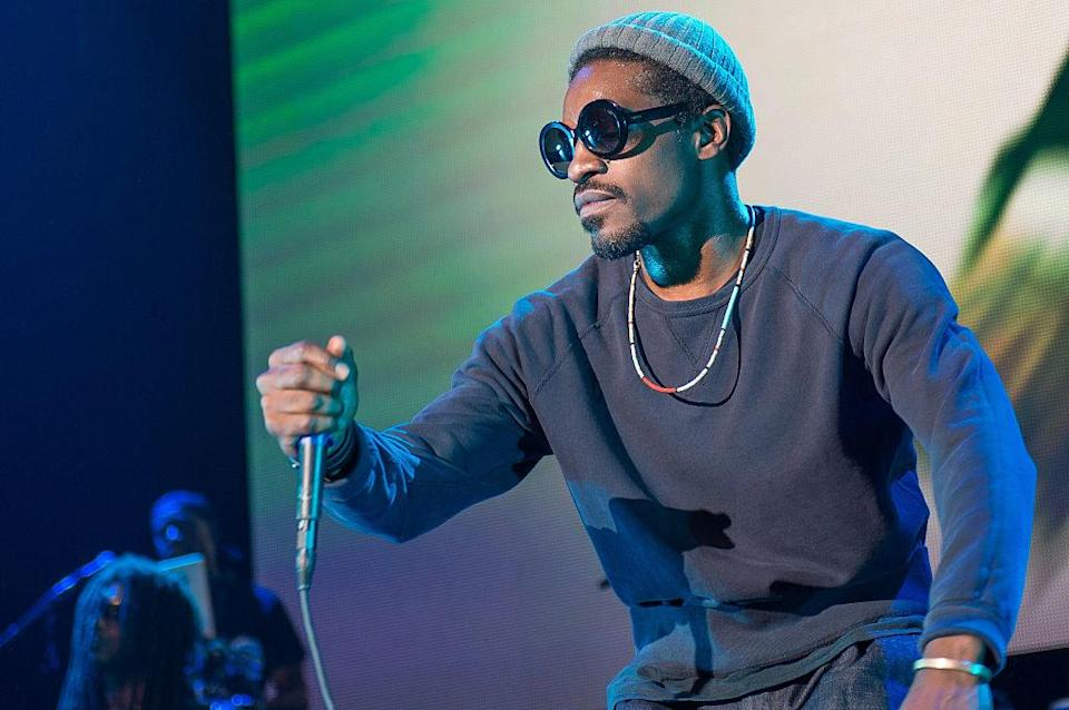 Andre performing on stage in a long-sleeved shirt, beanie, and sunglasses