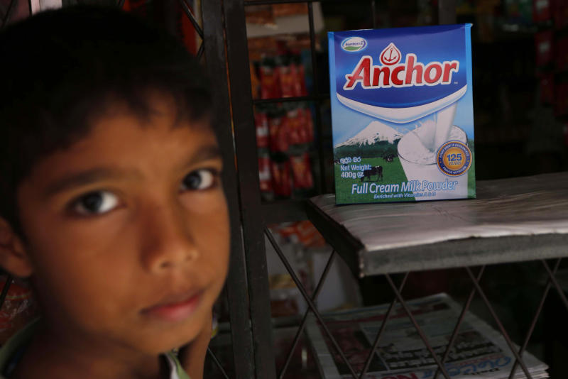 A Sri Lankan boy stands near a Fonterra product, which is still displayed for sale in Colombo, Sri Lanka, Tuesday, Aug. 6, 2013. Fonterra, the world's largest dairy exporter, announced Saturday that hundreds of tons of infant formula, sports drinks and other products sold in seven countries could be tainted. On Tuesday, Sri Lanka's health ministry said it had ordered all milk products imported from New Zealand be stopped at ports and the withdrawal of products with whey protein from supermarkets as a precaution after reports of contamination that could cause botulism. (AP Photo/Eranga Jayawardena)