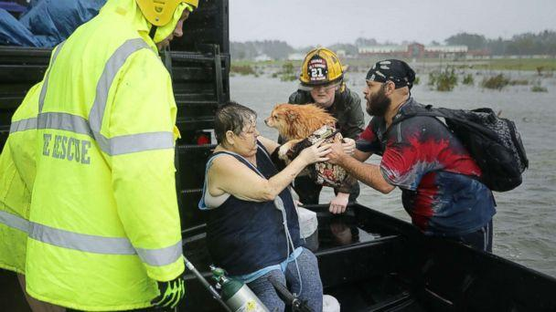 PHOTO: Rescue workers from Township No. 7 Fire Department and volunteers from the Civilian Crisis Response Team help rescue a woman and her dog from their flooded home during Hurricane Florence, Sept. 14, 2018, in James City, N.C. (Chip Somodevilla/Getty Images)