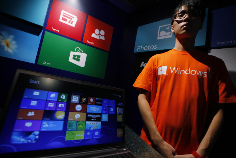 An attendant stands next to a computer running Microsoft Windows 8 operating system during its launching ceremony in Hong Kong Friday, Oct. 26, 2012. Microsoft launched a radical redesign of its world-dominating Windows operating system, introducing a touch-enabled interface that attempts to bridge the gap between personal computers and fast-growing mobile devices powered by the company's fiercest competitors. (AP Photo/Kin Cheung)