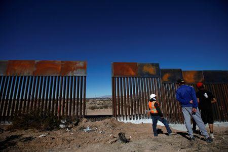 Worker chats with residents at a newly built section of the U.S.-Mexico border fence at Sunland Park, U.S. opposite the Mexican border city of Ciudad Juarez
