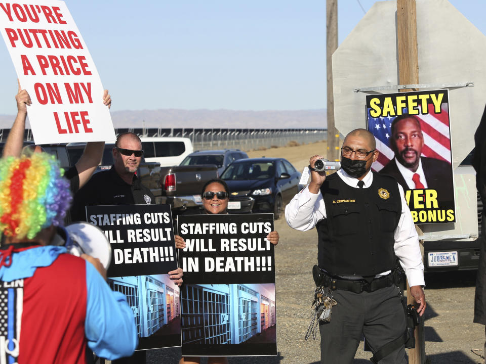 Special investigative services Lt. Armando Cervantes, right, films protesters at the Federal Correctional Institution at Mendota during a demonstration over staffing shortages, near the prison entrance in Mendota, Calif., Monday, May 17, 2021. (AP Photo/Gary Kazanjian)