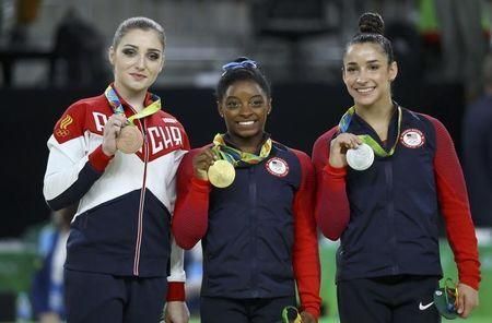 Simone Biles of the U.S., Alexandra Raisman of the U.S. and Aliya Mustafina of Russia pose with their medals. REUTERS/Mike Blake