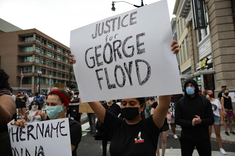 "WASHINGTON, USA - MAY 29: A person holds a banner reading ""Justice for George Floyd"", as crowds gather to protest after the death of George Floyd in Washington D.C. United States on May 29, 2020. Floyd, 46, a black man, was arrested Monday after reportedly attempting to use a counterfeit $20 bill at a local store. Video footage on Facebook showed him handcuffed and cooperating. But police claimed he resisted arrest. A white officer kneeled on his neck, despite Floydâs repeated pleas of ""I can't breathe."" Former police officer Derek Chauvin was charged with third-degree murder and manslaughter, according to Hennepin County Prosecutor Michael Freeman. Minneapolis, Minnesota Mayor Jacob Frey said Friday he imposed a mandatory curfew because of ongoing protests regarding the death of George Floyd. (Photo by Yasin Ozturk/Anadolu Agency via Getty Images)"