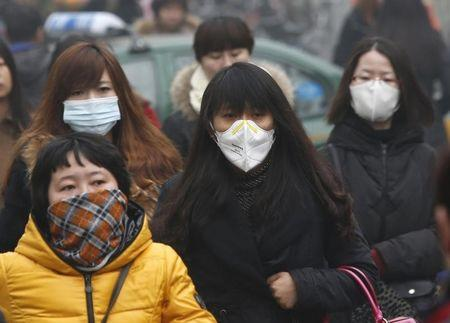 Commuters wearing masks make their way amid thick haze in the morning in Beijing