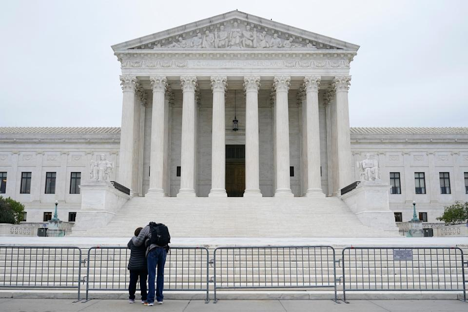 A woman and man pray outside the Supreme Court on Capitol Hill in Washington, D.C., on Oct. 27, 2020, a day after the Senate confirmed Amy Coney Barrett to become a Supreme Court justice.