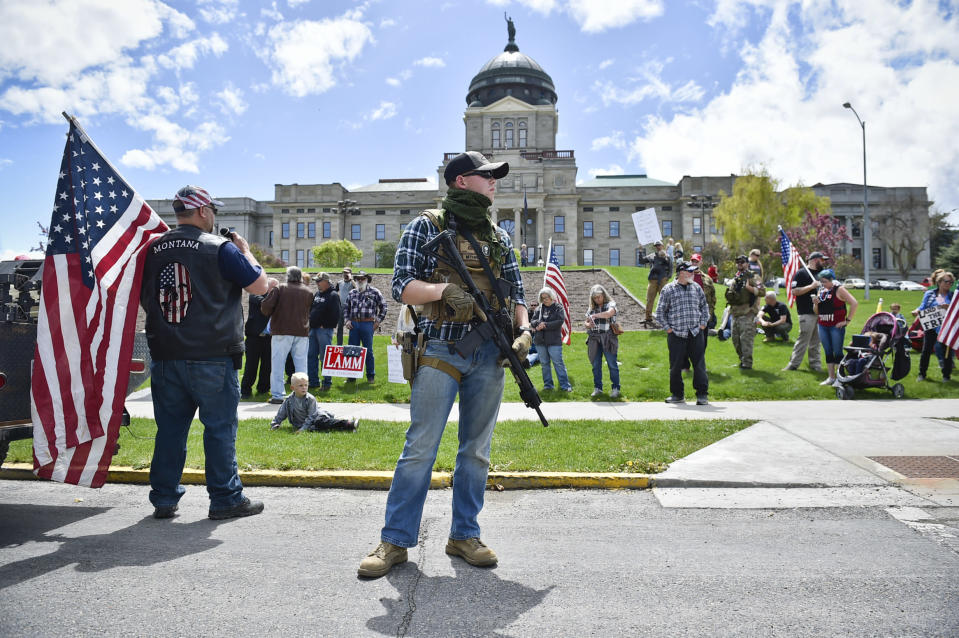 FILE - In this May 20, 2020 file photo protesters gather outside the Montana State Capitol in Helena, Mont. A bill signed into law Thursday, Feb. 19, 2021 by Montana Gov. Greg Gianforte allows concealed firearms to be carried in most places in the state without a permit, and it expands the list of places where guns can be carried to include university campuses and the state Capitol. (Thom Bridge/Independent Record via AP, file)