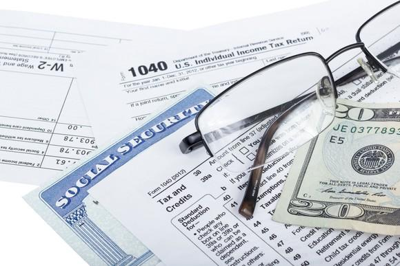 A Social Security card wedged between IRS tax forms and lying next to a pair of glasses and a twenty-dollar bill.