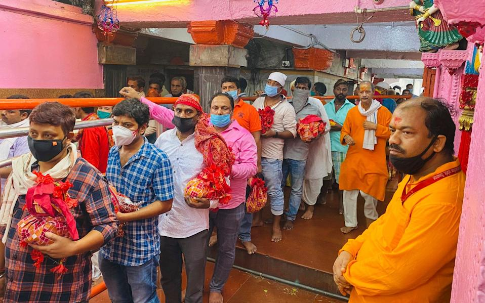 Devout Hindus wearing masks as a precaution against the coronavirus stand in a queue to offer prayers at the Vindhyavasini temple in Mirzapur in the northern Indian state of Uttar Pradesh, Saturday, Oct. 17, 2020. Health officials have warned about the potential for the coronavirus to spread during the upcoming religious festival season, which is marked by huge gatherings in temples and shopping districts. (AP Photo/Rajesh Kumar Singh)
