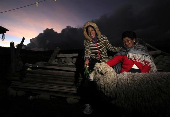 Marathon runner Gladys Tejeda, the first Peruvian athlete who qualified for the 2012 London Olympic Games, and her mother Marcelina Pucuhuaranga (R) feed a sheep at their home in the Andean province of Junin, May 13, 2012.
