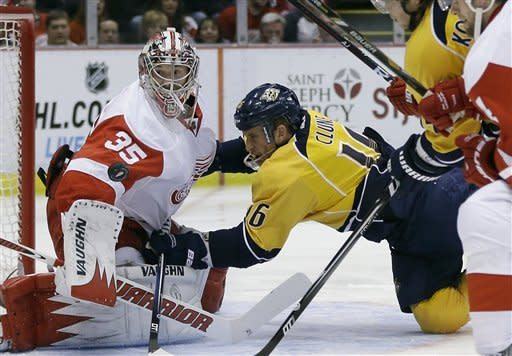 Detroit Red Wings goalie Jimmy Howard (35) deflects a shot as Nashville Predators left wing Richard Clune (16) falls into him during the first period of an NHL hockey game in Detroit, Saturday, Feb. 23, 2013. (AP Photo/Carlos Osorio)