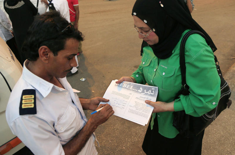 "In this Sunday, June 2, 2013 photo, an Egyptian police officer signs a petition for Tamarod, Arabic for ""rebel"", a campaign calling for the ouster of Egyptian President Mohammed Morsi and for early presidential elections in the Shubra neighborhood in Cairo, Egypt. Young activists are trying to rally public discontent with Egypt's Islamist President Mohammed Morsi by fanning out in the streets and collecting millions of signatures on a petition calling for his removal. Morsi's Muslim Brotherhood has dismissed the campaign as irrelevant, even illegal, but the signature drive has stirred up Egypt's politics as the president nears the end of his tumultuous first year in office. (AP Photo/Hassan Ammar)"