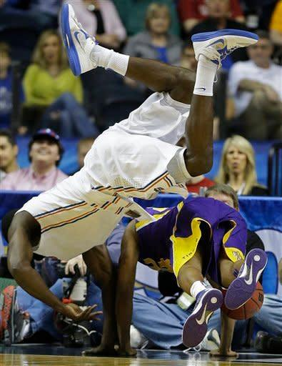 LSU guard Malik Morgan (24), right, and Florida center Patric Young (4) collide during the first half of an NCAA college basketball game at the Southeastern Conference tournament, Friday, March 15, 2013, in Nashville, Tenn. (AP Photo/John Bazemore)