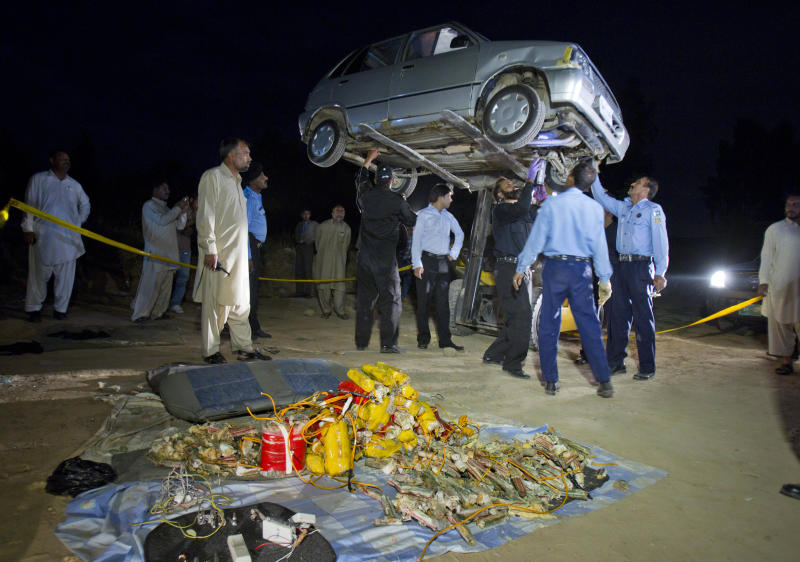 Pakistani police officers and explosive experts examine a car parked near the house of Pakistan's former President military ruler Pervez Musharraf, in Islamabad, Pakistan on Tuesday, April 23, 2013. Islamabad police chief Bani Amin says the explosive-laden vehicle was found parked about 150 meters (500 feet) from the main gate of Musharraf's house on the capital's outskirts Tuesday. (AP Photo/B.K. Bangash)
