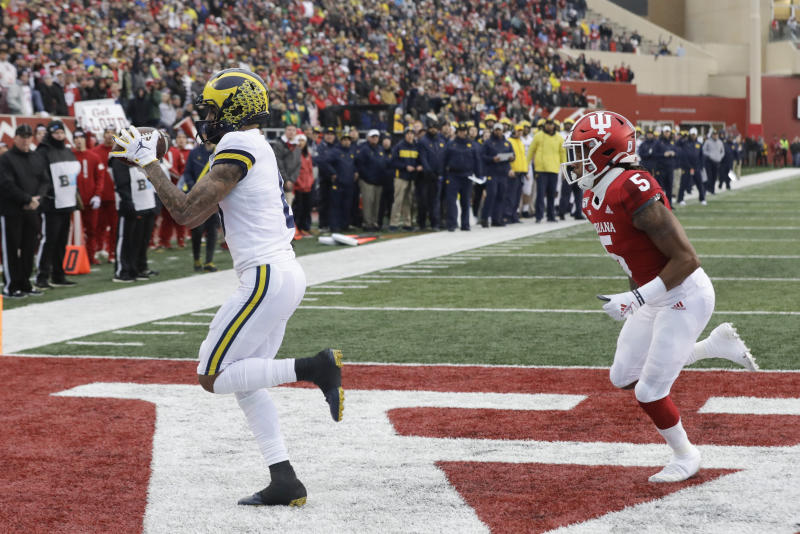 Michigan wide receiver Ronnie Bell (8) makes a touchdown reception against Indiana defensive back Juwan Burgess (5) during the first half of an NCAA college football game, Saturday, Nov. 23, 2019, in Bloomington, Ind. (AP Photo/Darron Cummings)