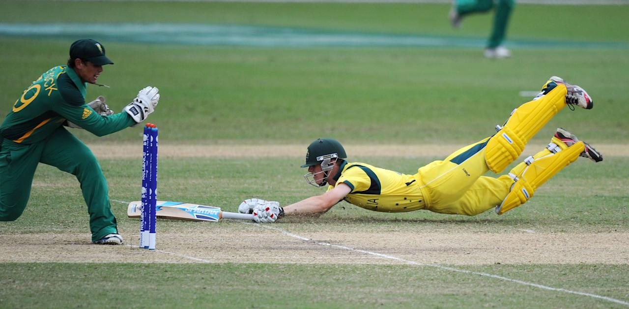 TOWNSVILLE, AUSTRALIA - AUGUST 21:  Cameron Bancroft of Australia dives to make his ground as Quinton De Kock (L) of South Africa attempts to run him out during the ICC U19 Cricket World Cup 2012 Semi Final match between Australia and South Africa at Tony Ireland Stadium on August 21, 2012 in Townsville, Australia.  (Photo by Malcolm Fairclough-ICC/Getty Images)