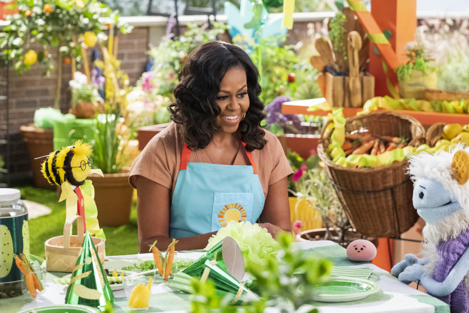 "This image released by Netflix shows former first lady Michelle Obama with Busy, a bee puppet, left, Mochi, a pink round puppet, and Waffles, a furry puppet with waffle ears on the set of the children's series ""Waffles + Mochi."" Obama is launching the new Netflix children's food show on March 16. (Adam Rose/Netflix via AP)"