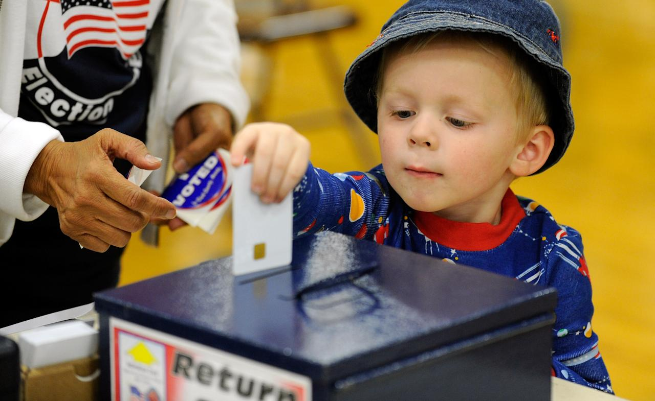 Zackary Lea, 3, returns his mother's authorization card after she cast her ballot at John Fremont Middle School on November 6, 2012 in Las Vegas, Nevada. Voting is underway in the battleground state of Nevada as President Barack Obama and Republican nominee former Massachusetts Gov. Mitt Romney remain in a virtual tie in the national polls. (Photo by David Becker/Getty Images)