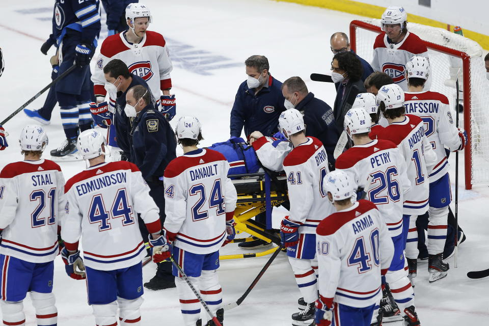 Montreal Canadiens' Jake Evans is taken off the ice on a stretcher after getting hit by Winnipeg Jets' Mark Scheifele during the third period of Game 1 of an NHL hockey Stanley Cup second-round playoff series Wednesday, June 2, 2021, in Winnipeg, Manitoba. (John Woods/The Canadian Press via AP)