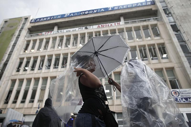 Supporters take cover from the rain in front of the Greek state television ERT headquarters in Athens, on Wednesday, June 12, 2013. State TV and radio signals were cut early Wednesday, hours after the government closed the Hellenic Broadcasting Corp., ERT, and fired its 2,500 workers. Greece's two largest labor unions called a 24-hour general strike for Thursday amid escalating protests against a decision to close state-run TV and radio that threw the country's conservative-led government into political crisis nearly a year after taking office. (AP Photo/Petros Giannakouris)