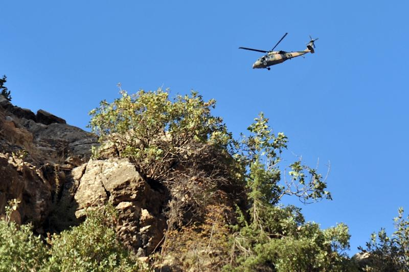 A military helicopter flies over a mountain in Yemisli, southeastern Turkey (AFP Photo/Mustafa Ozer)